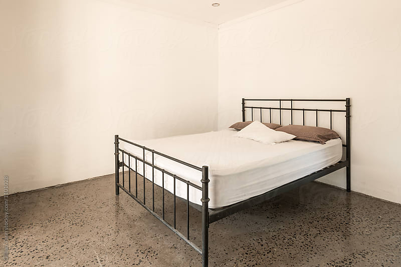 dormitary style accommodation, empty room with a large bed by Gillian Vann for Stocksy United