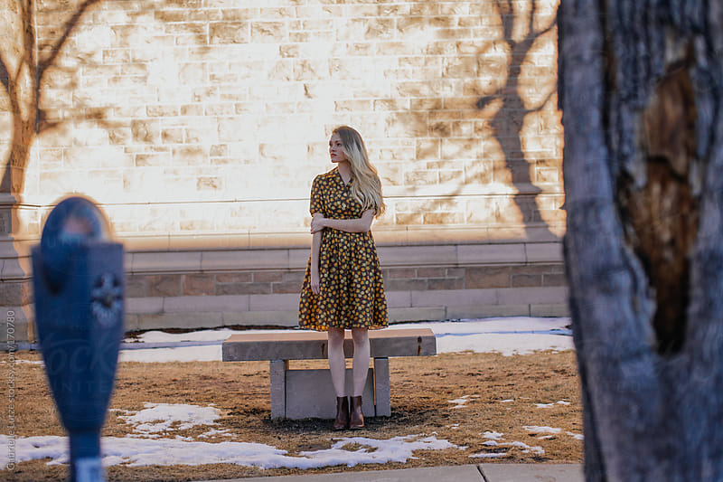 Beautiful Girl in Vintage Dress Waiting by a Bench by Gabrielle Lutze for Stocksy United