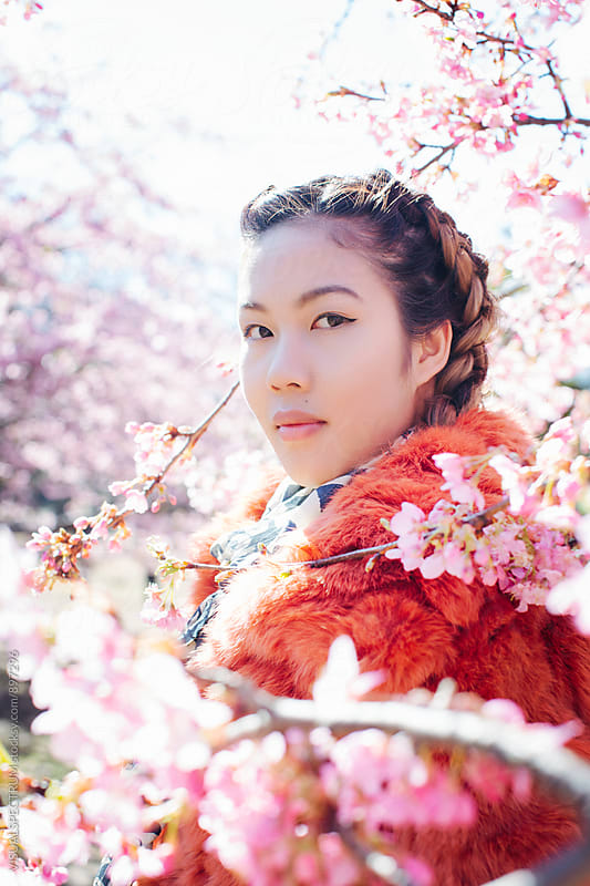 Outdoor Portrait of Pretty Young Japanese Woman Standing Next to Blossoming Sakura Tree by VISUALSPECTRUM for Stocksy United