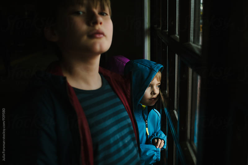 Two boys watch and wait by a window. by Julia Forsman for Stocksy United