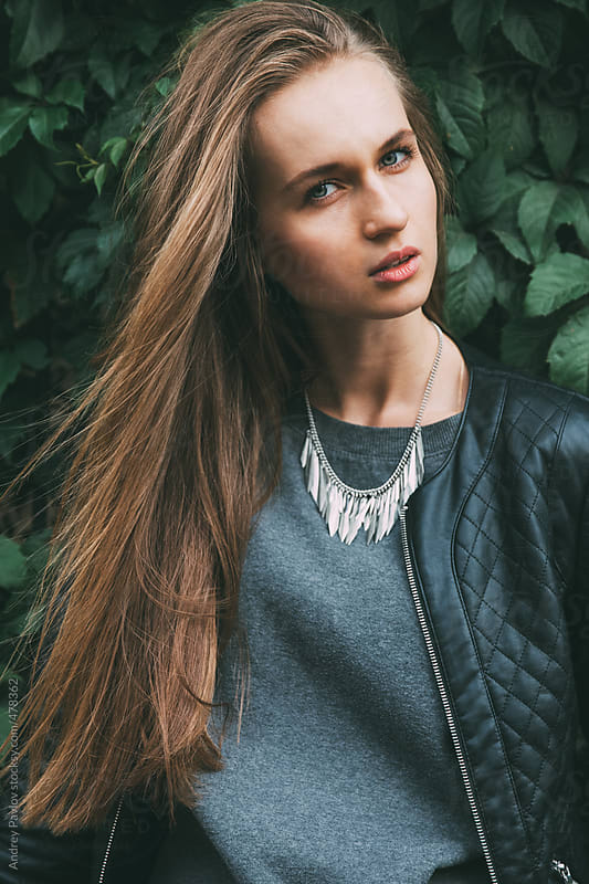 Female model looking at camera on a background of Ive by Andrey Pavlov for Stocksy United
