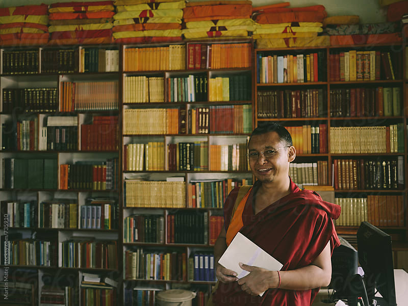 Smiling Monk Librarian in front of his Library by Martin Matej for Stocksy United
