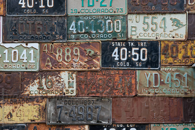 Vintage Colorado license plates mounted on an exterior wall by Mick Follari for Stocksy United