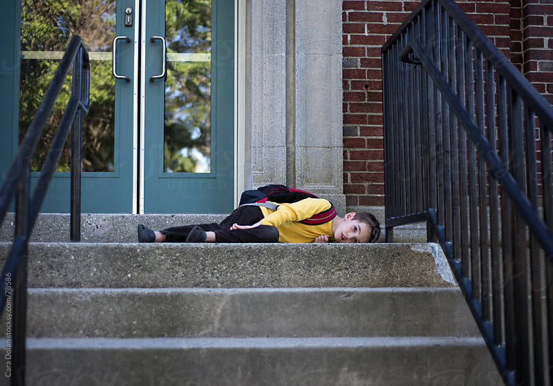 Child wearing red backpack lies down on the school steps, refusing to go inside by Cara Dolan for Stocksy United