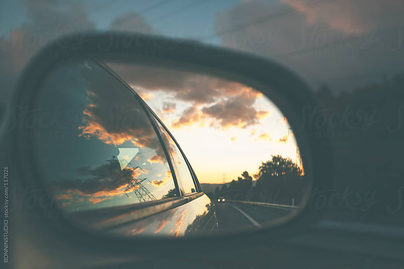 View of a sunset from the rearview of a car. by BONNINSTUDIO for Stocksy United