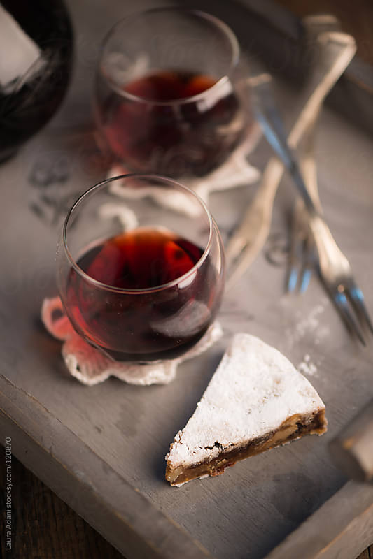 a slice of Panforte and a glass of marsala wine by Laura Adani for Stocksy United