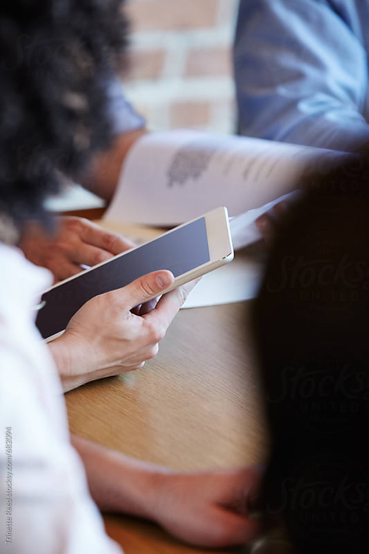 Businessman holding digital tablet in group meeting by Trinette Reed for Stocksy United