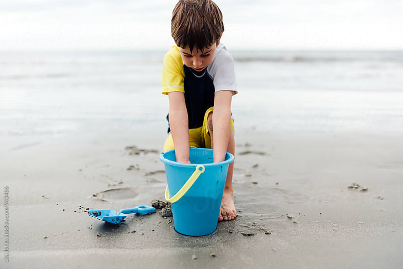 boy with hands in bucket, on the beach by Léa Jones for Stocksy United