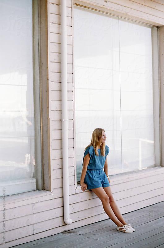 Girl sitting on the window-sill of the cafe by Lyuba Burakova for Stocksy United