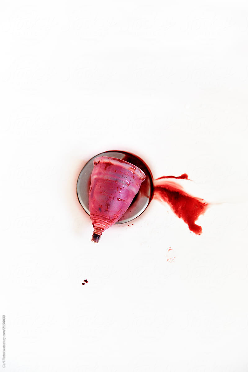 Menstrual cup emptied into a sink drain by Carli Teteris