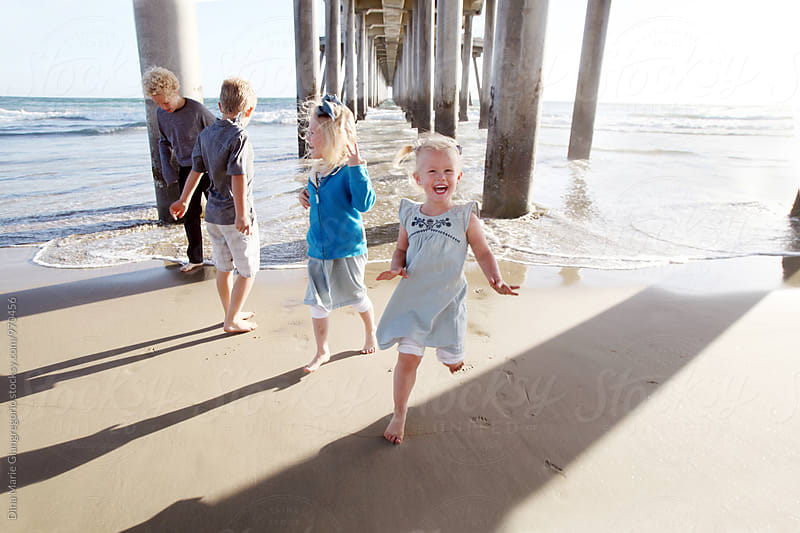 Kids Playing Near Beach Pier Laughing by Dina Giangregorio for Stocksy United