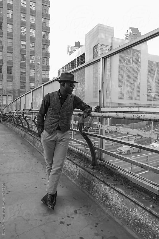 Young stylish man looking over a bridge by Eddie Pearson for Stocksy United