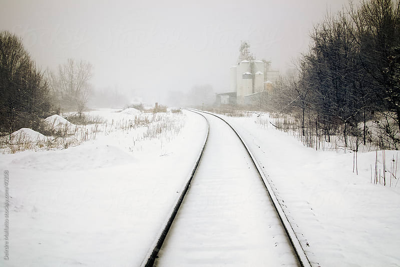 Train tracks and grain silos in snow by Deirdre Malfatto for Stocksy United