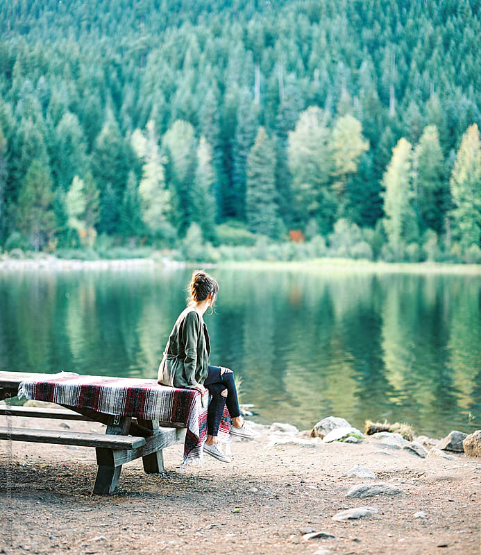 Girl sitting on picnic table at lake by Daniel Kim Photography for Stocksy United