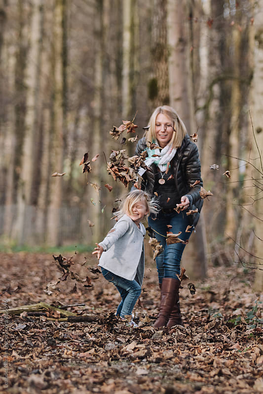 cute little girl and her mom throwing around with foliage in autumnal forest by Leander Nardin for Stocksy United