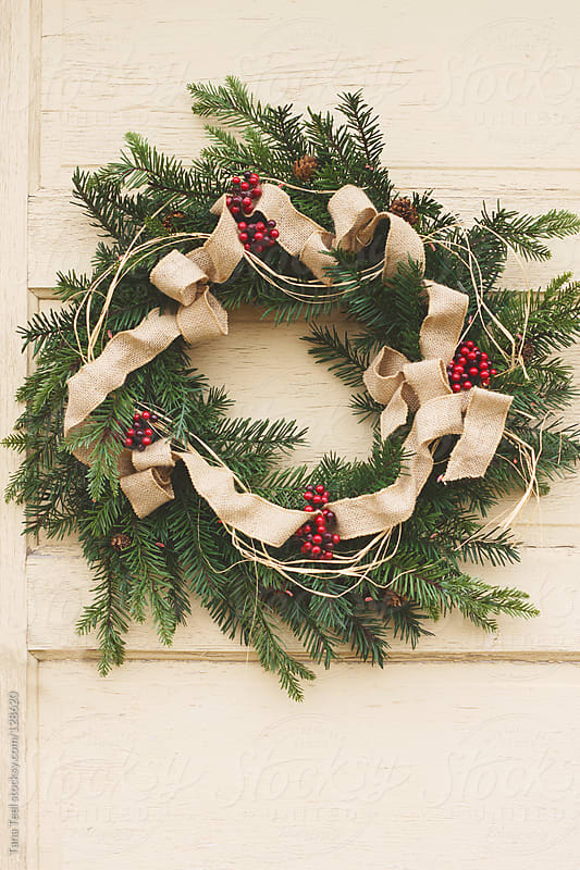 A rustic evergreen wreath hangs on an old door by Tana Teel for Stocksy United