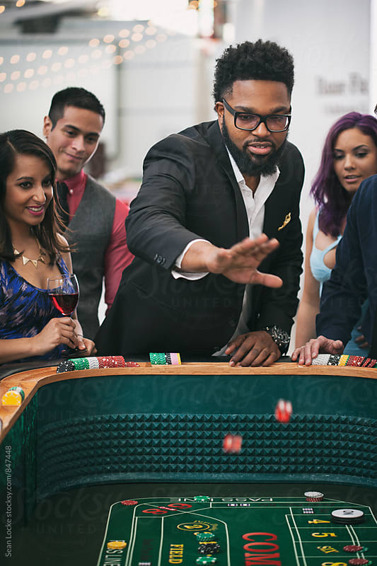 Casino: Handsome Man Throws Dice In Game Of Craps by Sean Locke for Stocksy United