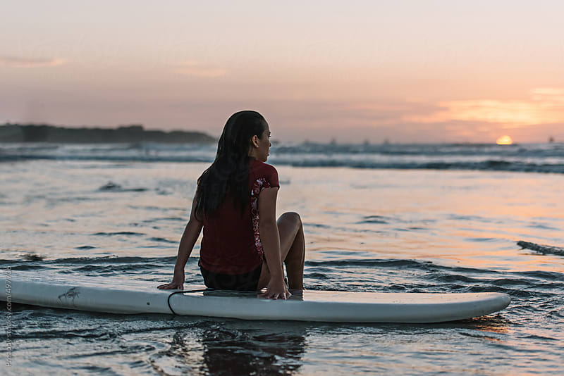 Surfer girl at sunset by Preappy for Stocksy United