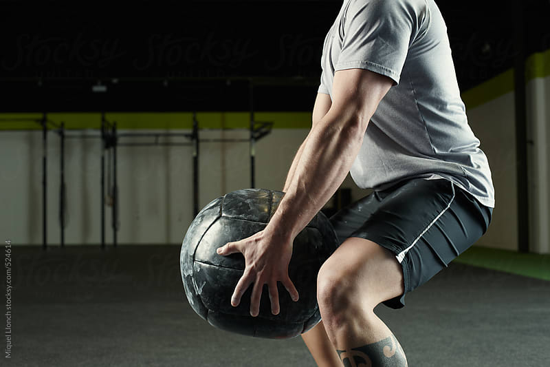 Fit man holding a heavy training ball in a gym by Miquel Llonch for Stocksy United