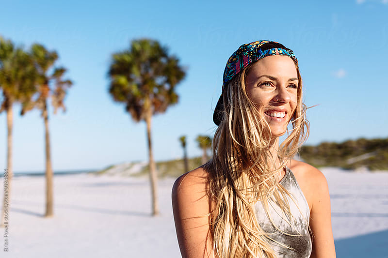 smiling woman on beach by Brian Powell for Stocksy United