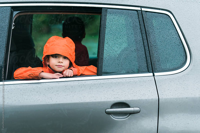 young child waiting inside a car while it rains outside by Tara Romasanta for Stocksy United