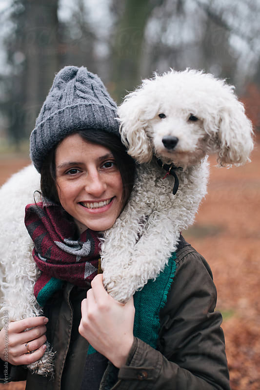 Portrait of a beautiful brunette woman with her white dog outdoors by VeaVea for Stocksy United
