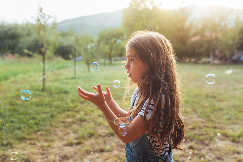 Child with bubbles on a field.  by Dejan Ristovski for Stocksy United