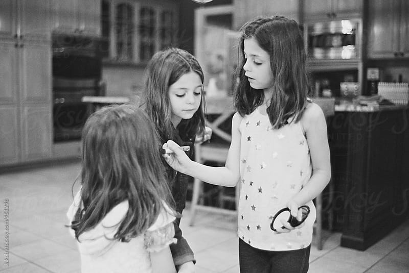 Three cute girl putting on make up by Jakob for Stocksy United
