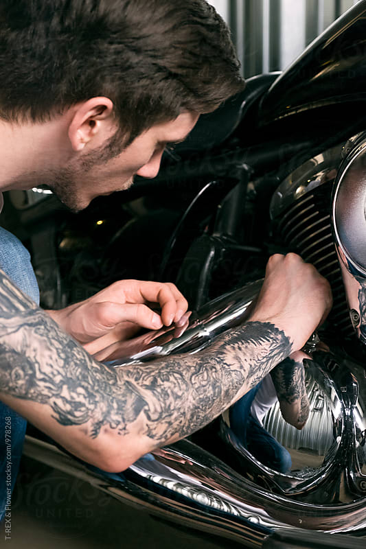 Close-up of tattooed man fixing bike by Danil Nevsky for Stocksy United
