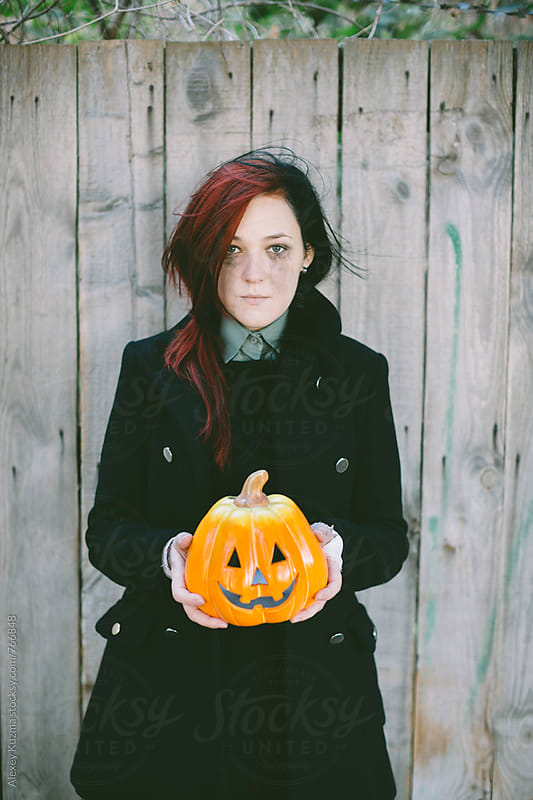 portrait of young woman with pumpkin by Alexey Kuzma for Stocksy United