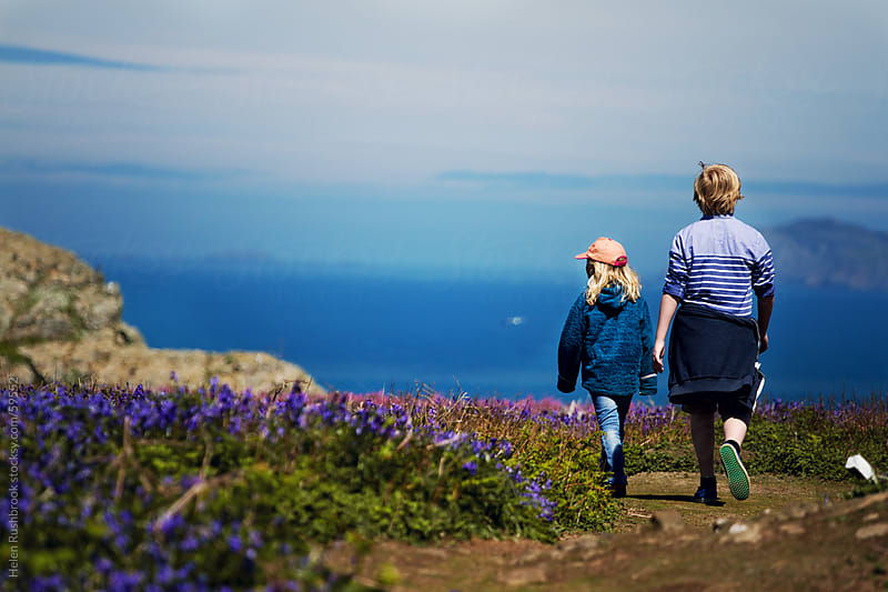 A boy and a younger girl walking through wildflowers by Helen Rushbrook for Stocksy United