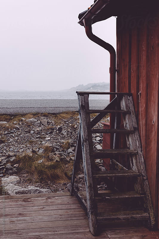 Ladder at a boat house looking out on the foggy sea by Jonas Räfling for Stocksy United