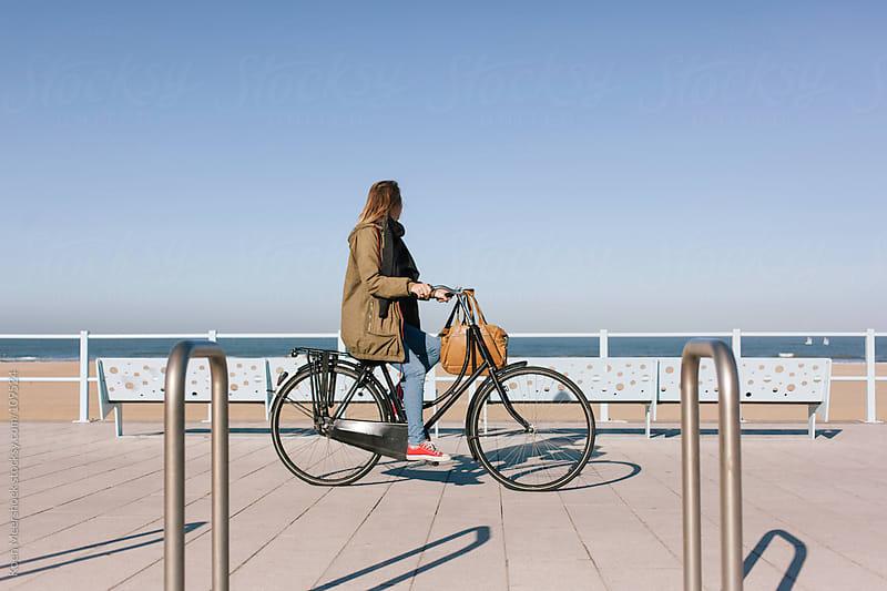 Woman riding on her bicycle looking to the ocean. by Koen Meershoek for Stocksy United