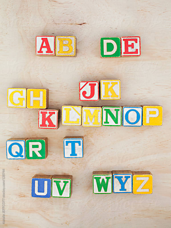 sorting out vintage wooden blocks into the alphabet by Natalie JEFFCOTT for Stocksy United