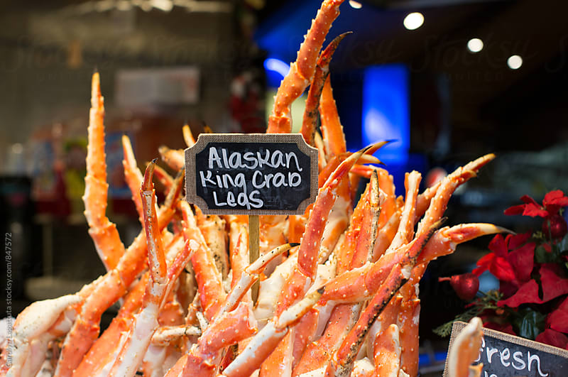 Alaskan king crab legs being sold at an outdoor market by Carolyn Lagattuta for Stocksy United