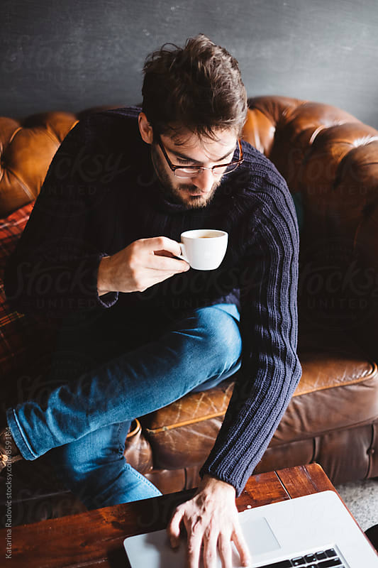 Handsome Man Working on His Computer While Drinking Coffee by Katarina Radovic for Stocksy United