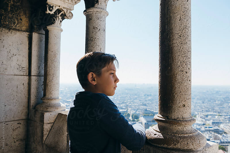 Side view of handsome boy looking away from basilica Sacre Coeur by Trent Lanz for Stocksy United
