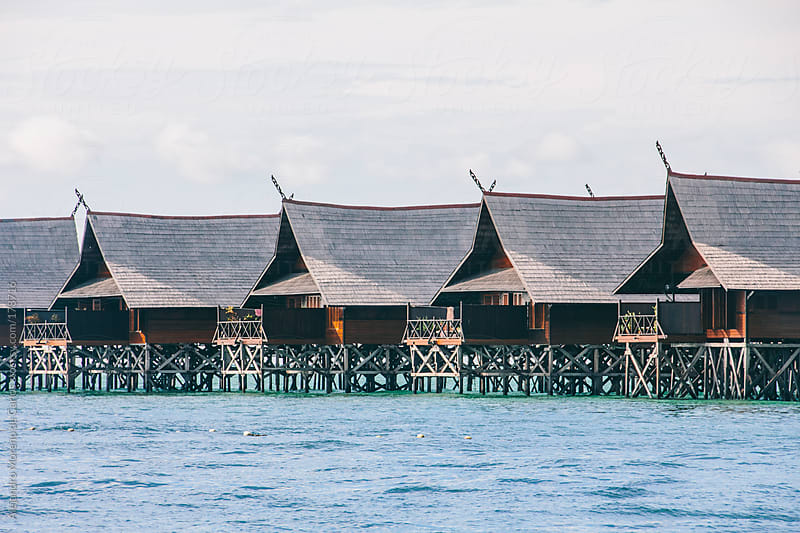 Resort over water bungalows on the sea on exotic tropical island by Alejandro Moreno de Carlos for Stocksy United