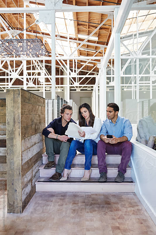 Millennial business people sitting on stairs for a meeting by Trinette Reed for Stocksy United