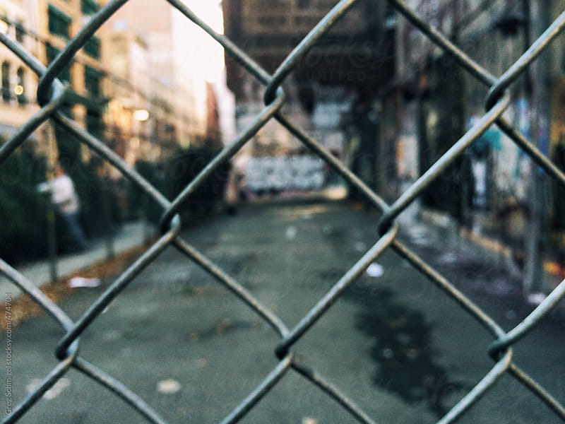 Cityscape and graffiti seen through a chain linked fence by Greg Schmigel for Stocksy United