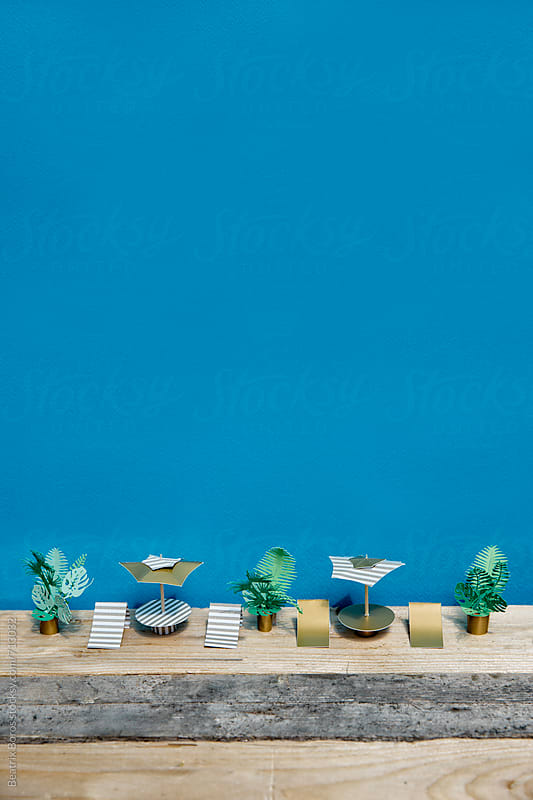 Some golden umbrellas and chairs in front of a blue wall by Beatrix Boros for Stocksy United