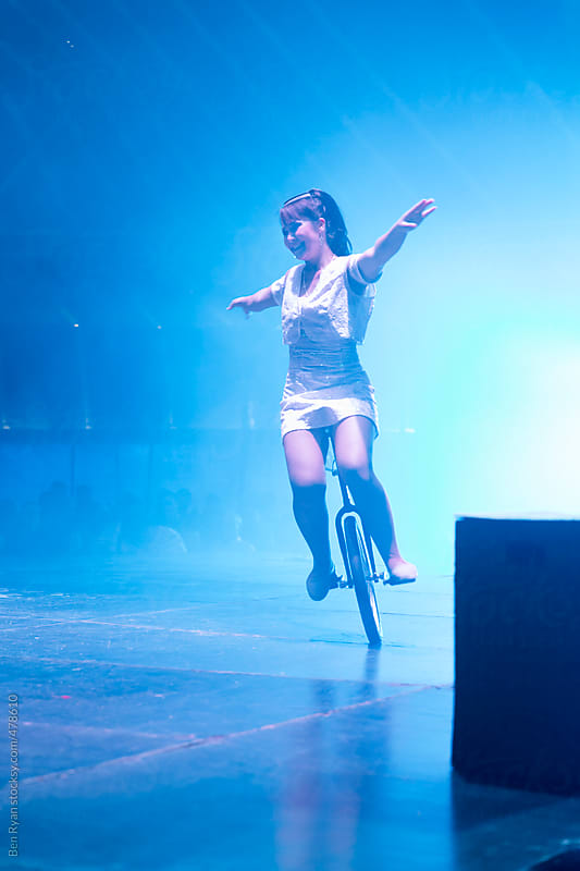 Circus performer on unicycle with blue smoke by Ben Ryan for Stocksy United