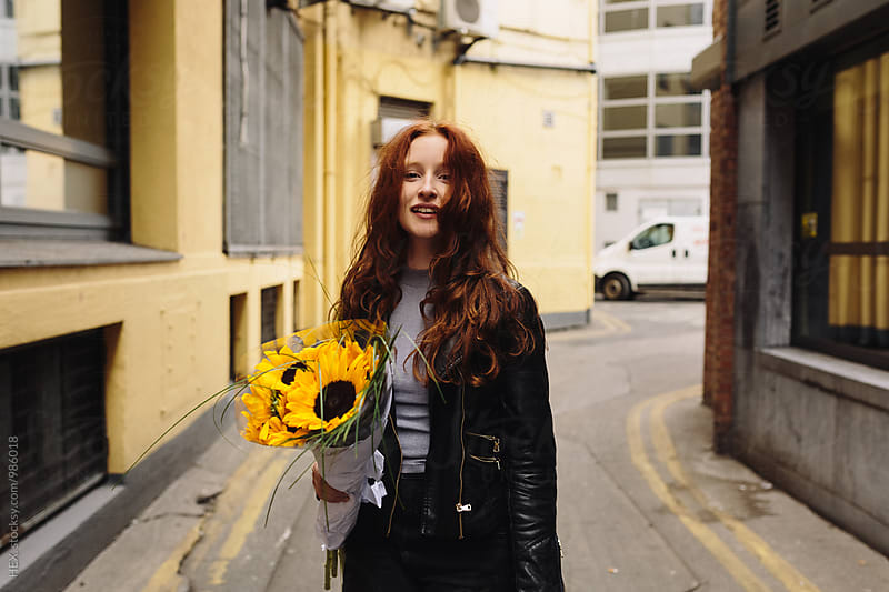 Beautiful Redhaed Girl Walking in the City with Sunflowers by Mattia Pelizzari for Stocksy United
