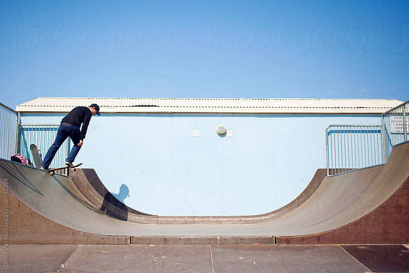 Young man skateboarding in a skate park on a sunny day by Denni Van Huis for Stocksy United