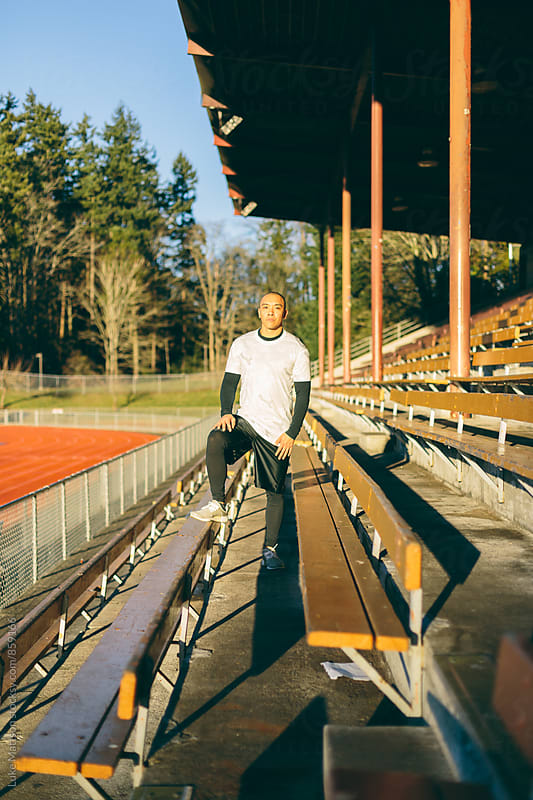 Athletic Man Standing Between Bleachers At Track And Field Stadium by Luke Mattson for Stocksy United