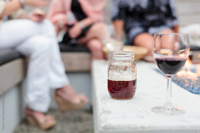 A beer-filled jar sits on the edge of a firepit at an outdoor party. by Holly Clark for Stocksy United