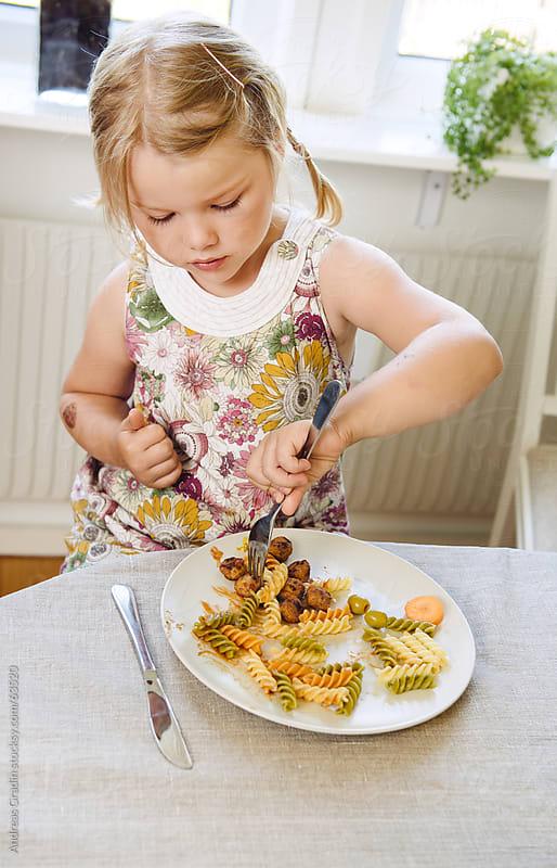 little girl eating pasta dinner by Andreas Gradin for Stocksy United