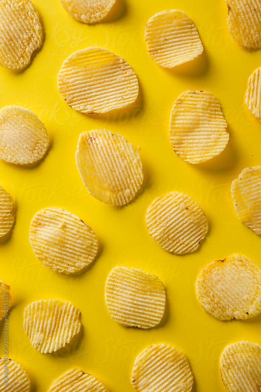 Potato chips on yellow background.  by BONNINSTUDIO for Stocksy United