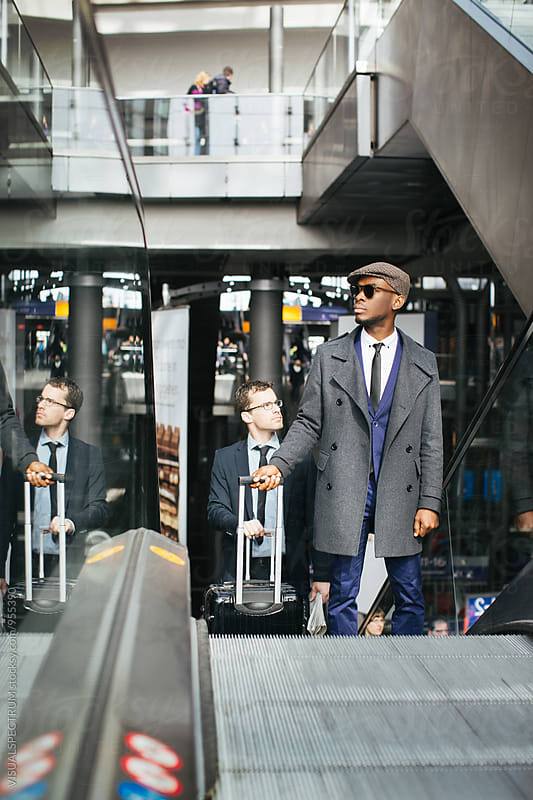 Caucasian and Black Businessman Coming Up Escalator in Modern Airport by VISUALSPECTRUM for Stocksy United
