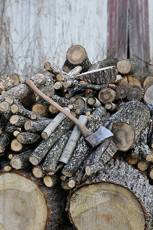 A stack of wood and axe piled for firewood by Sandra Cunningham for Stocksy United